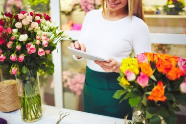 Florist using touchpad and standing by workplace, close up stock vector