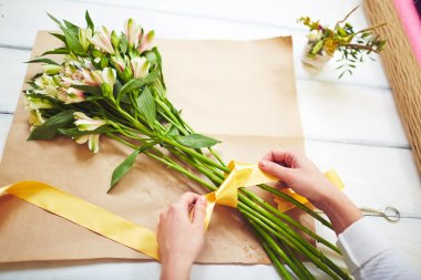 florist tying up bouquet with ribbon