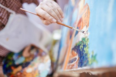 artist with paintbrush painting on canvas