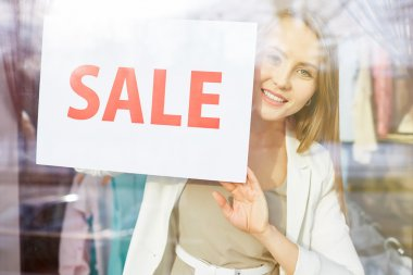 woman holding paper with sale announcement