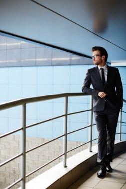 businessman standing by railings