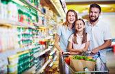 Rodina s nákupním vozíkem v supermarketu