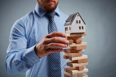 Businessman touching tower from small blocks