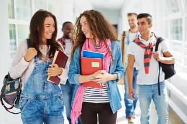 teenage girls walking along college corridor