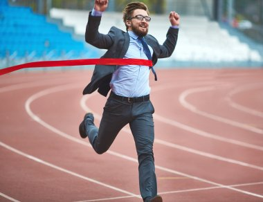 businessman reaching finish ribbon