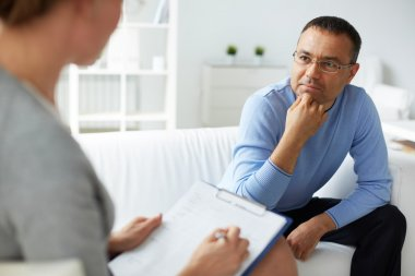 man in eyeglasses listening to psychologist