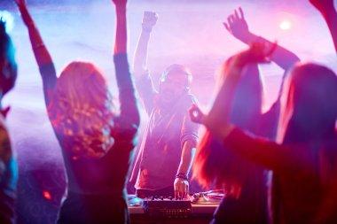 Energetic deejay and dancing crowd