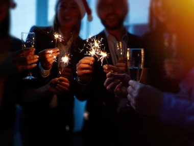 colleagues with champagne and Bengal lights