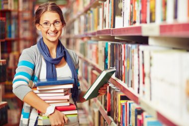 Teenager with stack of books