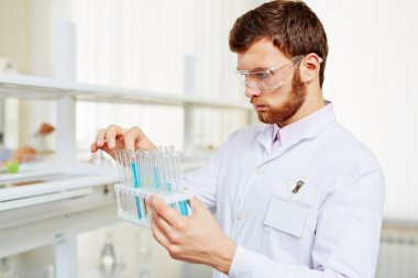 Chemist with flasks making experiment