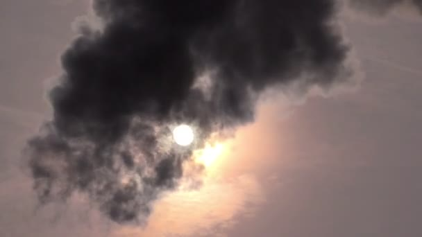Tmavý kouř proti obloze a slunce