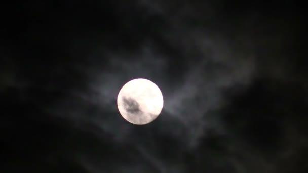 Měsíc na černé noční oblohu a plující oblaka