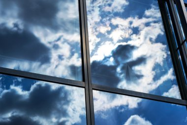Reflection of the sky and clouds in the windows of a building stock vector
