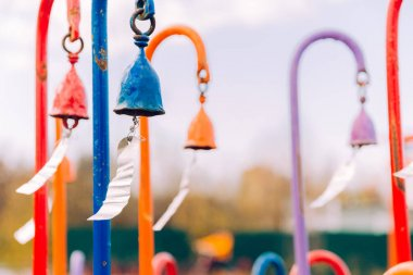 multi-colored wind chimes with metal plates that create a beautiful sound from the wind. selective focus.