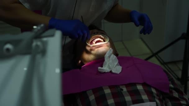 Der Zahnarzt entfernt mit Ultraschall Zahnstein und harte Beläge auf den Zähnen.
