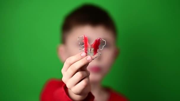 Devítiletý chlapec drží zubní štítek, ohavnost a ukázku zubní destičky..