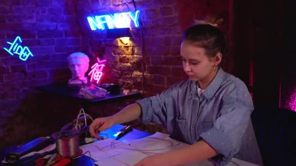 Mladá krásná dívka dělá neonové cedule v dílně. Talentovaný umělec pracující v mnohobarevném neonovém studiu. Mistr používá profesionální zařízení, nářadí a dráty.
