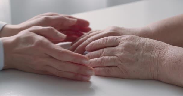 Video zeigt, wie jüngere Frauen ältere Hände in ihre nehmen und als beruhigende und unterstützende Geste zusammenhalten