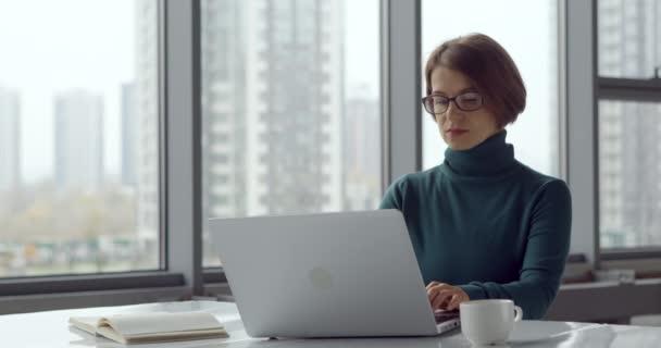 Üzletasszony nézi a monitor képernyőn, miközben dolgozik az irodában egy laptop.