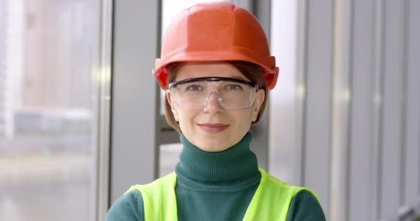 Porträt einer arbeitenden Frau mit Bauhelm. Das Gesicht einer glücklichen Ingenieurin.