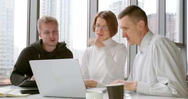 Ein Team von Geschäftsleuten bei einem Meeting macht Brainstorming und schaut auf den Laptop-Bildschirm. Kollegen bei der Arbeit besprechen das Projekt im Büro. Eine Frau und zwei Männer entwickeln gemeinsam eine Idee.