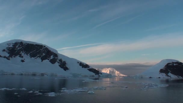 Antarctica. Snow covered Antarctic mountains in the Lemaire Channel at sunset