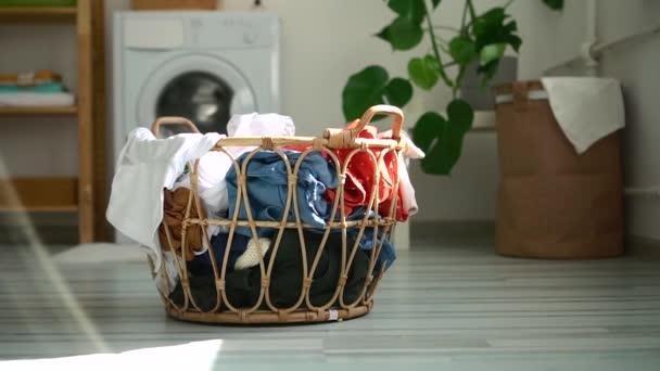 Egy kosár koszos ruha áll a padlón a mosókonyhában otthon..