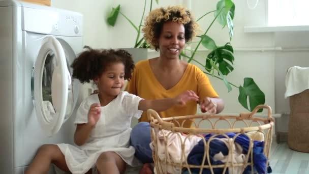 Glückliche Familie aus Mutter und Tochter erledigt Hausarbeit in Wäscherei zu Hause spbd.