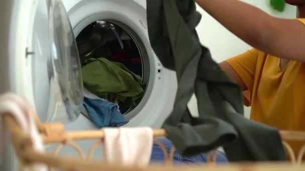 Hand einer nicht wiederzuerkennenden Afrikanerin, die eine Waschmaschine mit schmutziger Kleidung belädt. Hausfrau