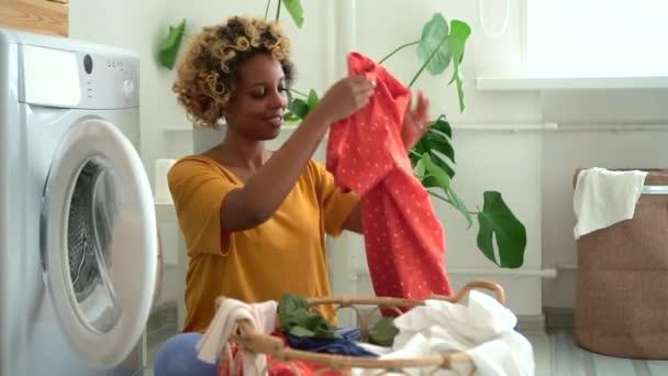 Gyönyörű fiatal nő tesz ruhákat mosógépbe, ül a padlón a mosókonyhában spbd.