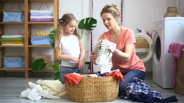 Mutter und Kind sortieren und bereiten gemeinsam Kleidung für die Wäsche vor. kleines Mädchen helfen Mama schmutzig waschen