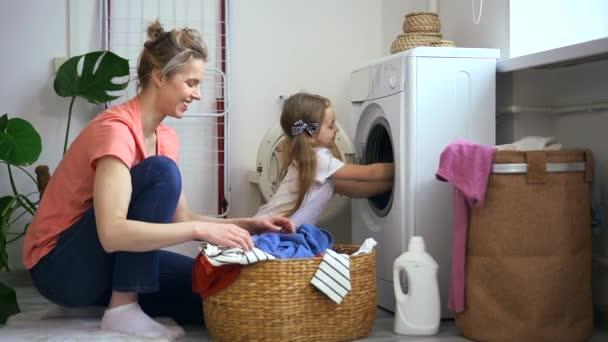 Dítě dcera zatížení pračka se špinavým oblečením Spbd. Kluk pomáhá šťastně se usmívající mámě. Vyprat