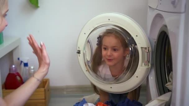 Mutter und tochter having spaß und sitting auf boden im zuhause wäsche drinnen spbd.