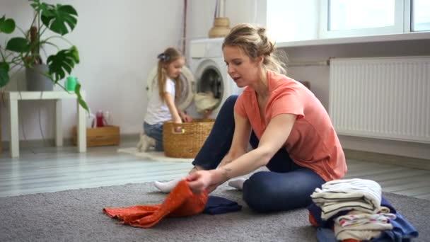 Frau faltet saubere Kleidung im Wohnzimmer, Tochter hilft beim Abladen der Waschmaschine. Spbd