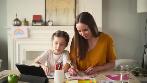 Matka a dcera kreslit tužkou v omalovánky společně, sedět za stolem s tabletem Spbd. Kluk
