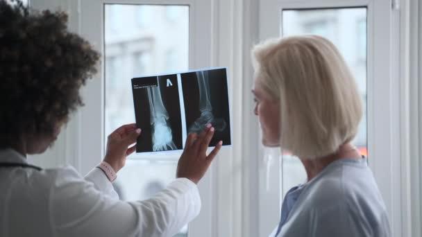 Arzt im Gespräch mit älterer Dame und Röntgenuntersuchung in moderner Klinik.