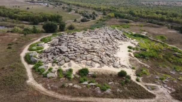 Letecký pohled. Hromada kamení na písku mezi plochým stepním krajem.