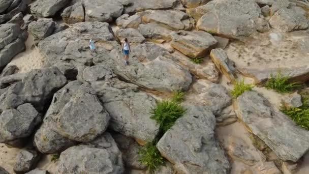 Letecký pohled. Máma a dítě chodí a šplhají na hromadu velkých kamenů. Mezi kameny je vidět písek. Slunečný den. Dívka a dítě jsou oblečeny v letním stylu, v kraťasech a šatech.