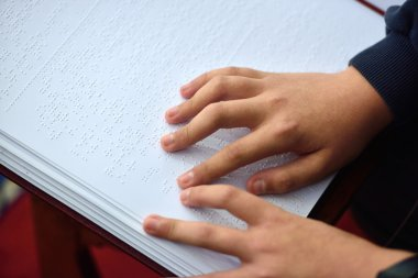 Blind child hand with a disability touch and read the cipher cod