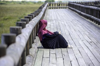 Female sitting on wooden path in nature