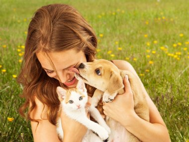 young girl holding kitten and puppy