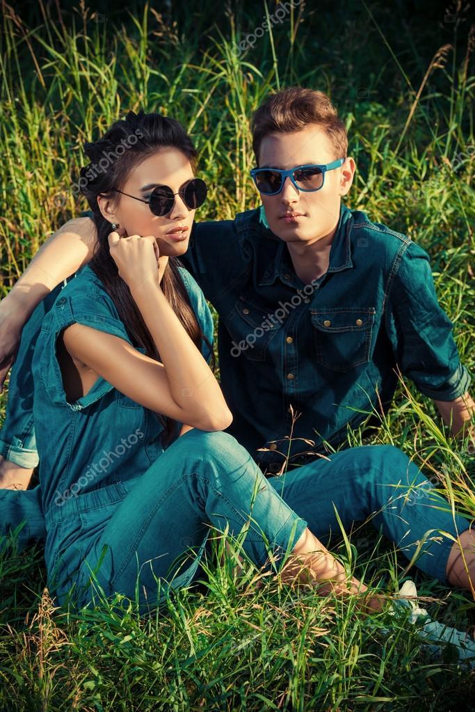 b556b33239a Atractiva pareja joven jeans ropa acostado relajado en una hierba. Disparo  de moda — Foto de ...