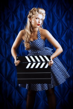 Pretty pin-up woman with retro hairstyle and make-up posing with clapper board over vintage background. stock vector