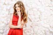 Fotografia fiori di carta. Bella ragazza in vestito rosso in posa da uno sfondo di fiori di carta bianco