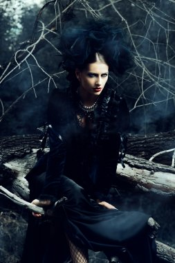 gothic beauty. Gorgeous gothic woman wearing long black dress posing in a mystic forest.