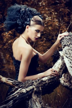 graceful lady. Gorgeous gothic woman wearing long black dress posing in a mystic forest.