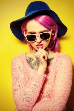 Pretty girl with crimson hair wearing bright clothes and sunglasses posing over yellow background. Bright style, fashion. Optics style. Tattoo. stock vector