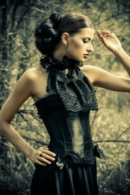 historical dress. Beautiful brunette woman in long black dress.