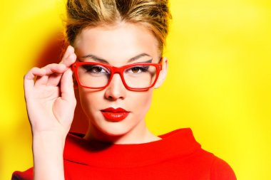 Close-up portrait of a stunning female model in red dress and elegant spectacles posing over yellow background. Beauty, fashion, optics. stock vector