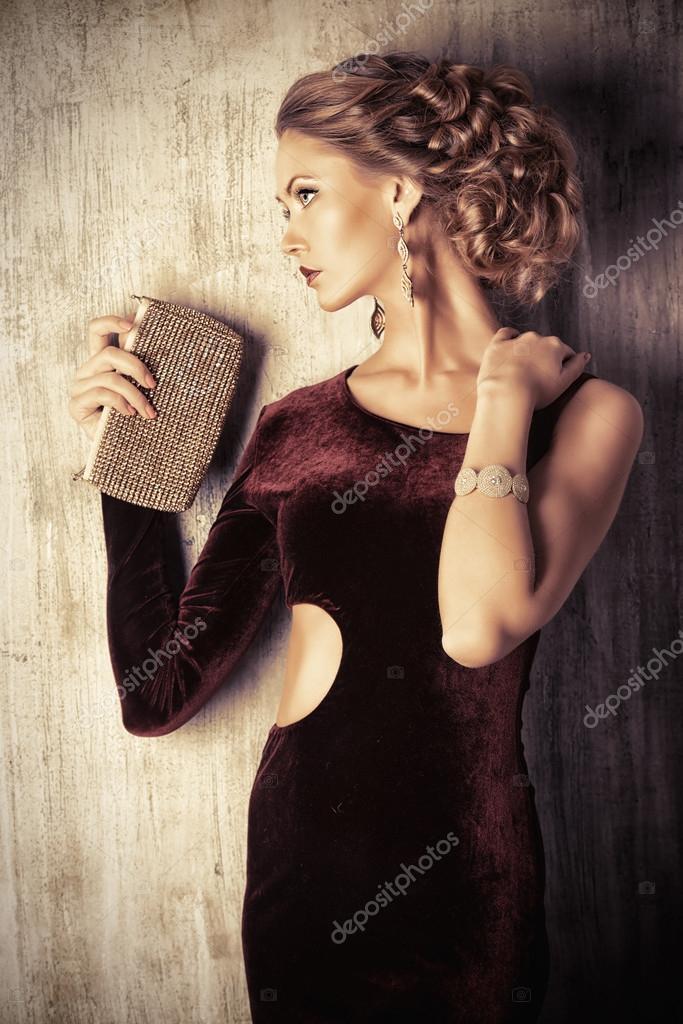Okouzlující mladá žena nosí elegantní večerní šaty a krásný účes. Klenoty.  Móda 3c869ad51e